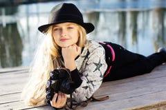 逗人喜爱的小女孩在有照相机的湖附近休息 图库摄影