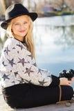 逗人喜爱的小女孩在有照相机的湖附近休息 免版税库存图片