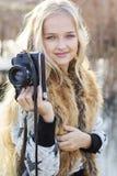 逗人喜爱的小女孩在有照相机的湖附近休息 库存图片
