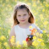 逗人喜爱的小女孩在有狂放的春天的一个草甸开花 免版税库存图片