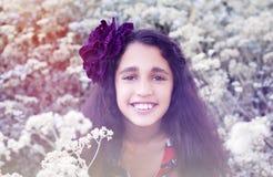 逗人喜爱的小女孩在有第一朵野花的春天公园 免版税库存图片