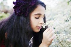 逗人喜爱的小女孩在有第一朵野花的春天公园 免版税库存照片