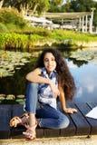 逗人喜爱的小女孩在池塘附近坐一个温暖和晴朗的夏天 免版税库存照片