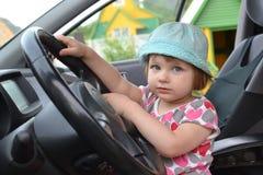 逗人喜爱的小女孩在汽车的轮子后坐 免版税库存照片