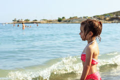 逗人喜爱的小女孩在海观看 免版税库存图片