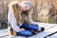 逗人喜爱的小女孩在湖附近休息 免版税库存图片
