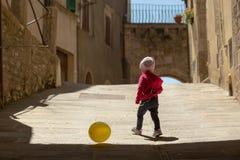 逗人喜爱的小女孩在红色使用穿戴了与在t的黄色气球 免版税库存图片