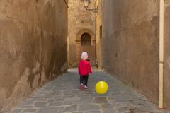 逗人喜爱的小女孩在红色使用穿戴了与在t的黄色气球 免版税库存照片