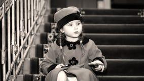 逗人喜爱的小女孩在老房子里面的减速火箭式外套穿戴了 免版税库存照片