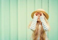 逗人喜爱的小女孩在船民帽子的绿松石墙壁附近站立并且看起来被发明的双筒望远镜 文本的空间 免版税库存照片