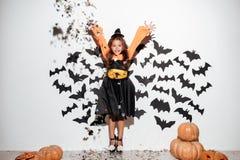 逗人喜爱的小女孩在获得万圣夜的服装穿戴了乐趣 库存图片