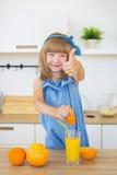 逗人喜爱的小女孩在蓝色礼服新闻中桔子和展示喜欢 免版税库存照片