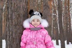 逗人喜爱的小女孩在降雪的森林里 图库摄影