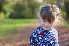 逗人喜爱的小女孩在绿色公园微笑并且看  免版税库存照片