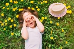 逗人喜爱的小女孩在绿色草坪说谎并且盖他的面孔用他的手 库存照片
