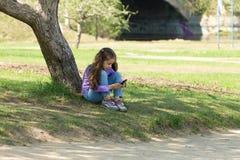 逗人喜爱的小女孩坐与一个手机的草在她的手和凝视上在电话的屏幕 免版税库存图片