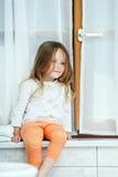 逗人喜爱的小女孩坐卫生间窗口 免版税库存照片