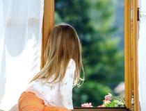 逗人喜爱的小女孩坐卫生间窗口 免版税图库摄影