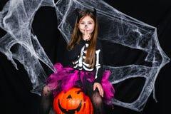 逗人喜爱的小女孩坐在黑背景的南瓜与蜘蛛网 库存照片