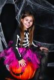 逗人喜爱的小女孩坐在黑背景的南瓜与蜘蛛网 库存图片