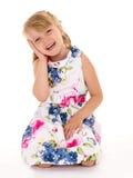 逗人喜爱的小女孩坐她的膝部 免版税库存照片