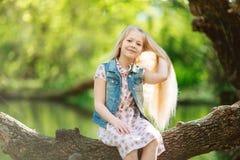 逗人喜爱的小女孩坐日志在河下 库存图片
