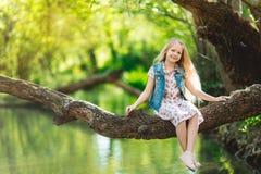 逗人喜爱的小女孩坐日志在河下 免版税库存图片