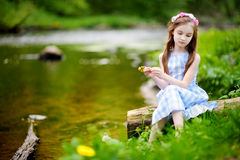 逗人喜爱的小女孩坐日志由一条河在晴朗的夏日 免版税图库摄影
