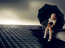 逗人喜爱的小女孩坐有伞的屋顶 免版税库存照片