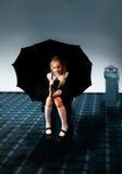 逗人喜爱的小女孩坐有伞的屋顶 免版税图库摄影