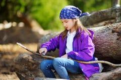 逗人喜爱的小女孩坐树日志使用一把小折刀消减一根远足的棍子 免版税图库摄影