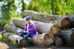 逗人喜爱的小女孩坐树日志使用一把小折刀消减一根远足的棍子 免版税库存照片