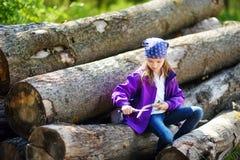 逗人喜爱的小女孩坐树日志使用一把小折刀消减一根远足的棍子 库存照片