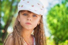 逗人喜爱的小女孩坐草 免版税库存照片