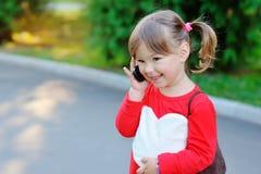 逗人喜爱的小女孩室外画象讲话由电话 免版税图库摄影