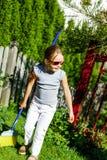 逗人喜爱的小女孩帮助的母亲在庭院里 库存照片