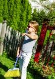逗人喜爱的小女孩帮助的母亲在庭院里 图库摄影