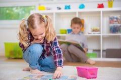 逗人喜爱的小女孩戏剧比赛,男孩读了书 免版税库存图片