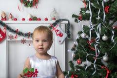 逗人喜爱的小女孩拿着红色莓果在新年圣诞节附近 免版税库存照片