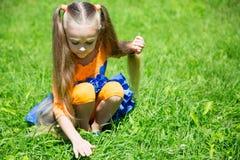 逗人喜爱的小女孩捉住一只蚂蚱 库存图片