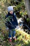 逗人喜爱的小女孩探索的秋天森林在春天小河之前 图库摄影