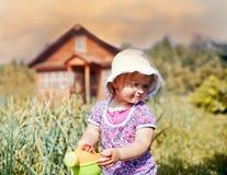 逗人喜爱的小女孩浇灌的庭院 免版税库存照片
