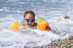 逗人喜爱的小女孩游泳在海 库存图片