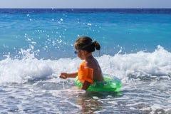 逗人喜爱的小女孩游泳在海 免版税图库摄影