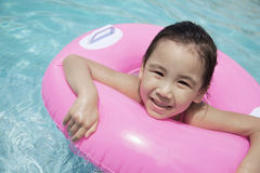 逗人喜爱的小女孩游泳的画象在水池的与一支桃红色管 免版税库存图片