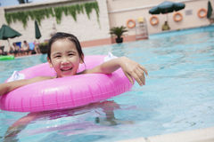 逗人喜爱的小女孩游泳的画象在水池的与一支桃红色管 库存图片