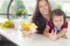 逗人喜爱的小女孩烹调与她的母亲的,健康食物 图库摄影