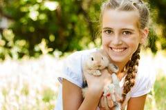 逗人喜爱的小女孩用一只兔子在庭院里。 库存图片