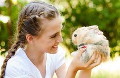 逗人喜爱的小女孩用一只兔子在庭院里。 免版税图库摄影