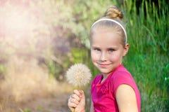 逗人喜爱的小女孩用在草甸的蒲公英 库存图片